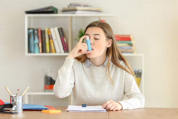 Picture of woman having an asthma attack using an asthma inhaler at home