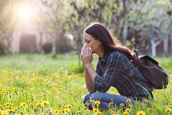 Photo of a young woman sitting in a field of flowers, blowing her nose
