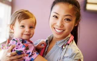 Photo of smiling female doctor holding a small child