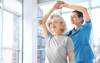 Photo of a young woman in scrubs lifting the arm of an elderly woman over her head.