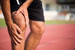 male runner clutching his knee
