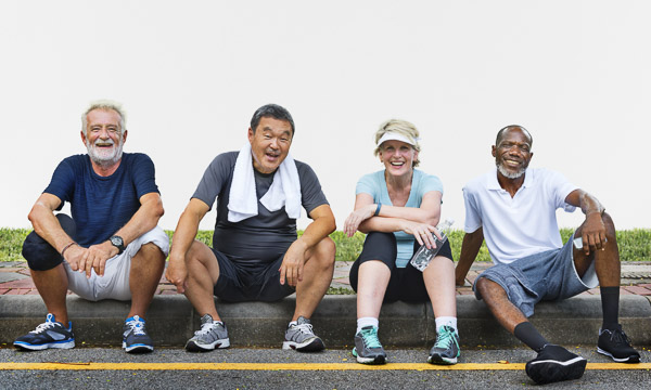 A photo of four smiling seniors in workout clothing resting on a streetcurb
