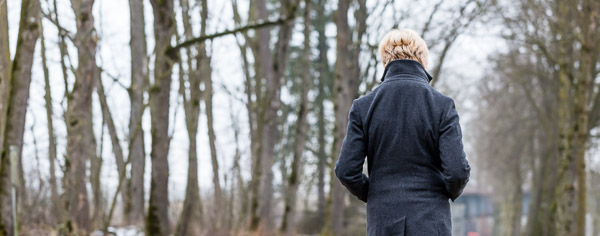 Photo of woman turned away from the camera in the woods during winter