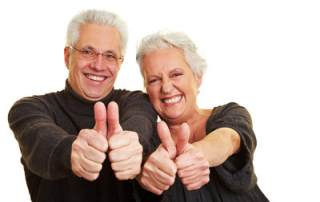 Photo of Two happy senior citizens holding their thumbs up